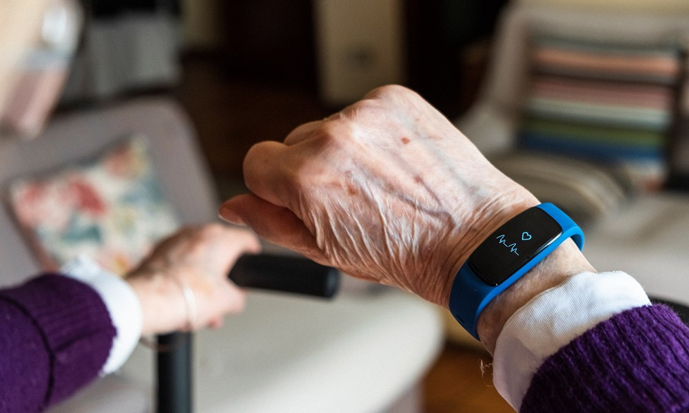 an elderly person holding up a piece of wearable tech